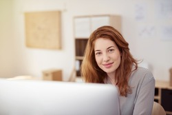 Pretty Blond Teen Girl Sitting at her Computer Table, Looking at the Camera with Happy Facial Expression.
