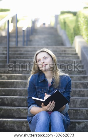 Pretty Blond Teen Girl Sitting on a Stairway Outdoors Writing in Journal