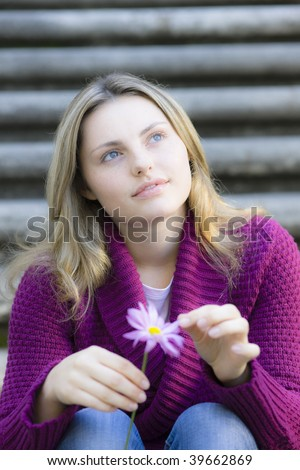 Pretty Blond Teen Girl Sitting on Stairs Holding a Daisy