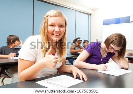 Pretty blond teen gives a thumbs up because she did well on a school test. - stock photo