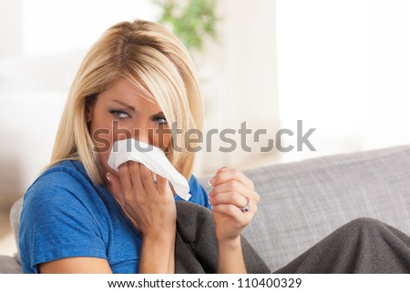 Pretty blond white female sitting on couch with a cold with gray blanket.
