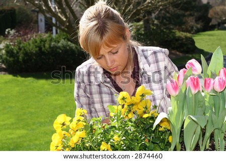 Pretty blond woman gardening outside.