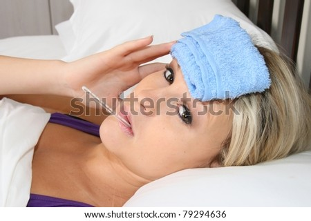 Pretty blond woman in bed with headache and thermometer in her mouth