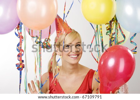 Pretty blond woman in red dress with balloons during a party smiling