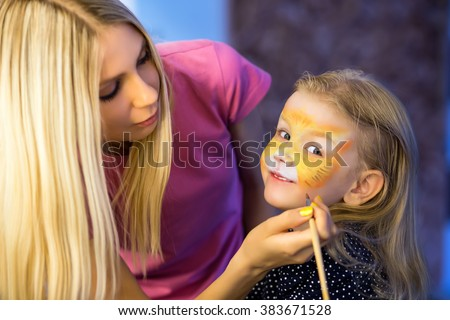 Pretty blond woman painting the face of a little girl #383671528