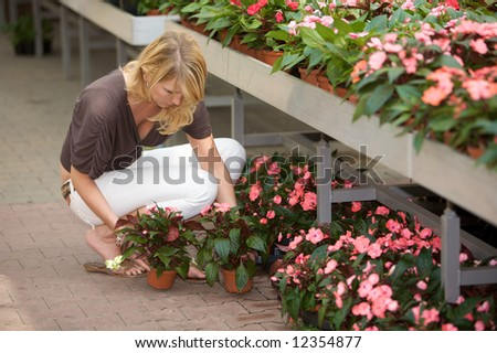 Pretty blond woman picking new plants in the gardening center