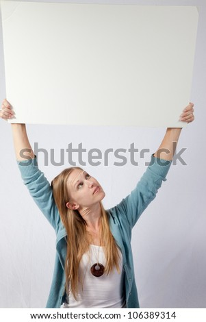 Pretty blond woman sitting and holding a blank sign over her head with a big smile, and looking up at the sign