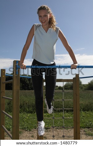 Pretty blond woman using the kids playground to do some exercises