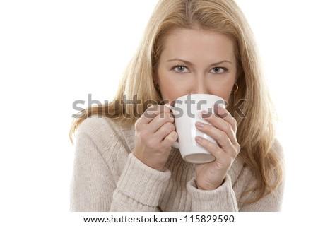 pretty blond woman wearing beige sweather drinking coffee