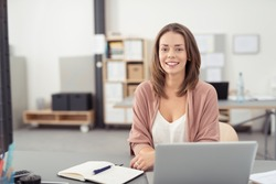 Pretty Blond Young Office Woman Sitting at her Desk with Notes and Laptop, Smiling at the Camera