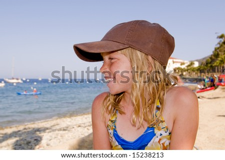 Pretty Blonde Girl in Ball Cap on a Gorgeous Beach.