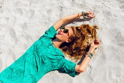 Pretty blonde girl lying on the tropical  sunny beach . Wearing cool stylish sunglasses, color    bo ho tunic and bright trendy accessories . Warm colors.