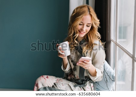 Pretty blonde girl sitting on window sill with cup of coffee, tea and smartphone in hands. She has long blonde wavy hair, smile and looking at her phone. Wearing beautiful silk pajama.