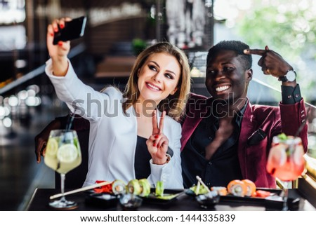 Pretty blonde girl taking a picture by the cell phone with sushi and mojito. Chenese eat, friends couple.