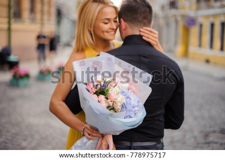 pretty blonde girl with a bouquet of flowers including roses, astilba, carnations and hydrange hugs her boyfriend #778975717
