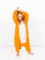 pretty blonde girl with cozy lion costume is posing in front of white wall