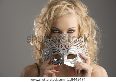 pretty blonde girl with curly hair takes one silver mask, she is in front of the camera, takes the mask on the mouth and looks in to the lens