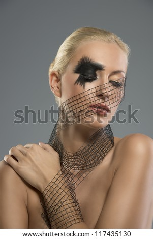 Pretty blonde girl with dark make-up and grid around the neck, the face and wrist. She looks down at left and her left hand is on the right shoulder