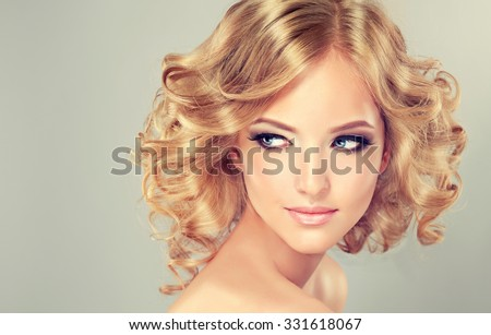 Pretty blonde girl with hairstyle  curled hair .Hairstyle medium length .  hair styling