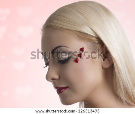 pretty blonde girl with sexy clothing and heart shaped decoration on the face, her face is turned at right and she looks down at right