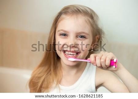 pretty blonde girl 7-8 years old brushing her teeth Stock photo ©