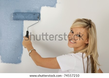Pretty blonde lady painting a bedroom room powder blue color