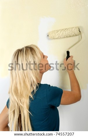 Pretty blonde lady painting a wall an ivory color