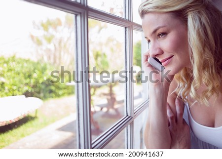 Pretty blonde sitting by the window on a phone call at home in the living room #200941637