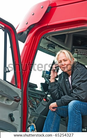 Pretty blonde truck driver getting directions to a delivery site on her cellphone.