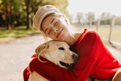 Pretty blonde with her beloved dog spending time together outdoor in the autumn. Nice portrait of a beautiful woman and her pet in the park.