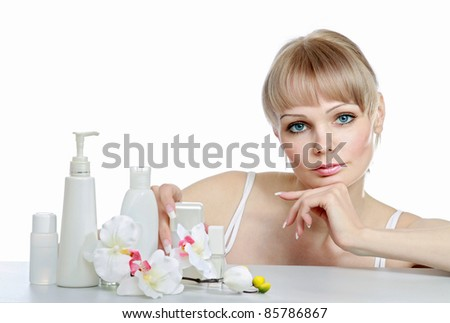 Pretty blonde with skincare products isolated on white background