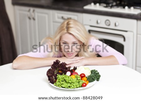 Pretty blonde woman eating some vegetables in the kitchen in her apartment