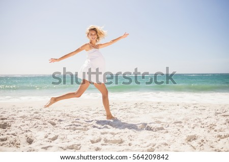 Pretty blonde woman jumping on the beach