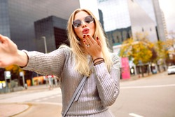 Pretty blonde woman making selfie in the street near modern buildings area, wearing grey sweater and glamorous accessories, sending air kiss, romantic mood, happy tourist woman, spring autumn time.