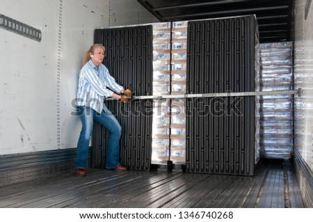 Pretty blonde woman placing a load-lock in the inside of a trailer to secure the loaded pallets during the upcoming trip. #1346740268