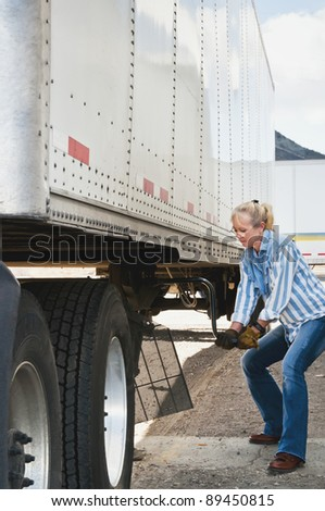 Pretty blonde woman truck driver cranking the dolly handle to raise the legs of a trailer after backing her tractor under it.