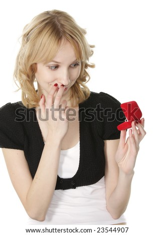 Pretty blonde young woman looking at ring in box with surprise