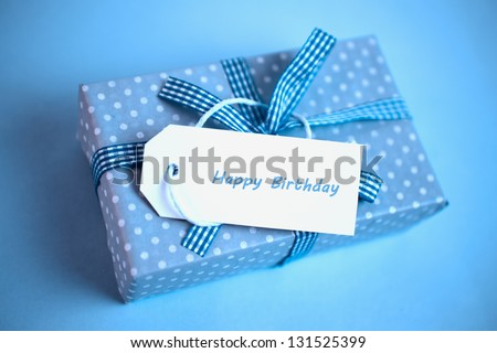Pretty blue gift with a happy birthday card on a blue background close up
