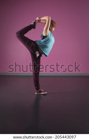 Pretty break dancer stretching leg behind head in the dance studio