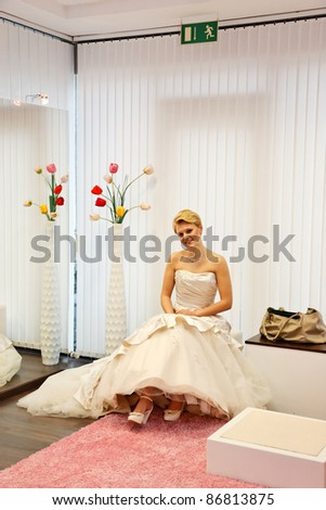 Pretty bride  in a wedding gown in the bridal shop.