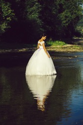pretty bride pretty woman in long elegant white lace wedding dress stands in lake water sunny day outdoor on natural background