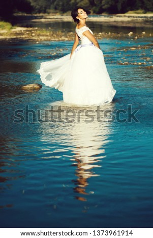 pretty bride pretty woman in long elegant white lace wedding dress stands in lake water sunny day outdoor on natural background #1373961914