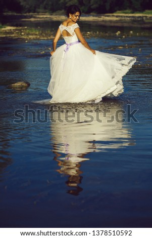 pretty bride pretty woman in long elegant white lace wedding dress stands in lake water sunny day outdoor on natural background #1378510592