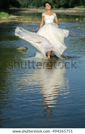 pretty bride pretty woman in long elegant white lace wedding dress stands in lake water sunny day outdoor on natural background #494265751