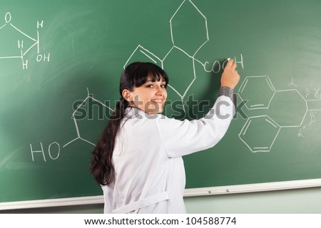 Pretty brunette drawing chemical structure on a chalkboard