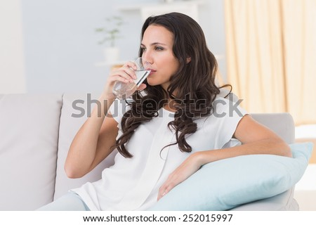 Pretty brunette drinking water on couch at home in the living room