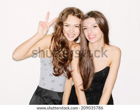 Pretty brunette girl friends having fun. Both looking at camera and smiling (laughing). One showing sign with hand. Inside