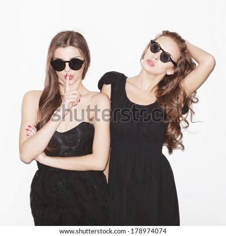 Pretty brunette girl friends having fun. Bright makeup and pink lips. Wearing sunglasses. One showing silence sign. Both looking at camera. Inside