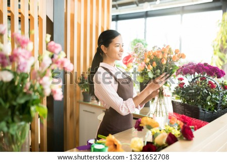 Pretty brunette girl in apron looking at big rose bouquet in her hands while making floral bouquets in florist shop
