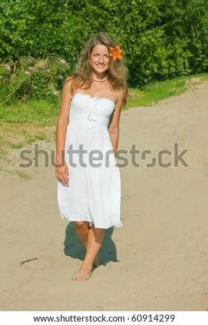Pretty brunette girl on rural road during summer day